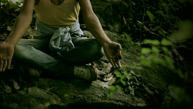 Young man doing meditation yoga in woods.